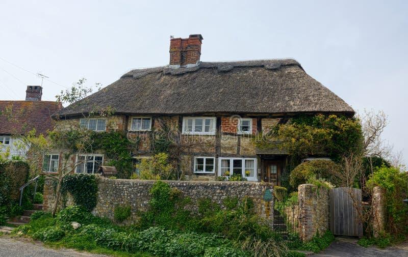 Met stro bedekt roofed plattelandshuisje en ommuurde tuin het UK royalty-vrije stock afbeeldingen