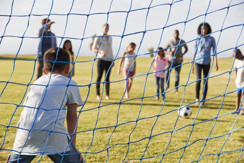 Meta de defensa del muchacho durante un partido de fútbol de la familia fotografía de archivo libre de regalías