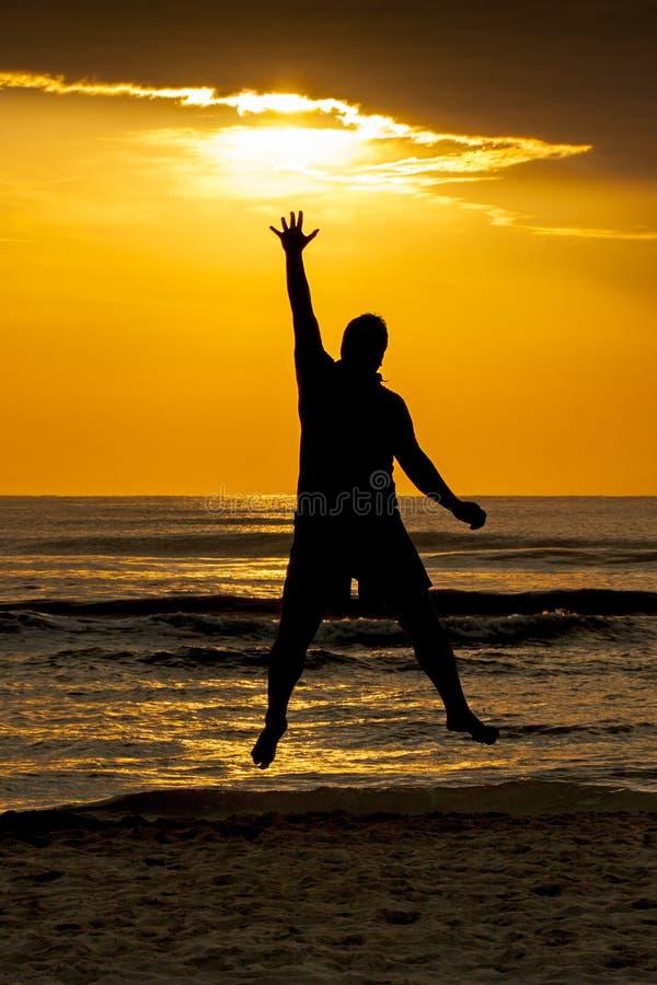 Meta de salto de Sun del tacto del mar del hombre de la silueta imágenes de archivo libres de regalías