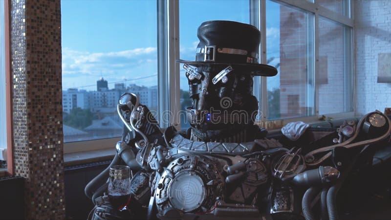 Metaal androïde zitting bij lijst in restaurant met glas wijn op achtergrond van mening van high-rise gebouwen van stad royalty-vrije stock foto's