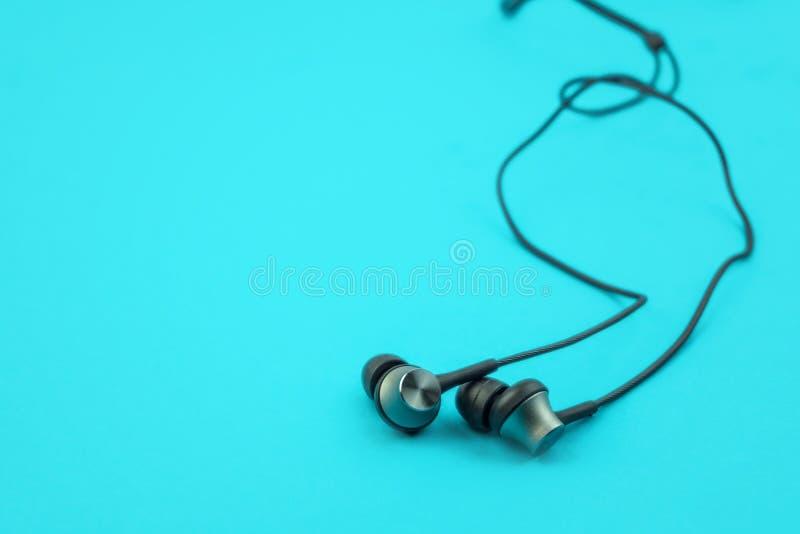 Metaal earbuds en draden op blauwe achtergrond, lage hoek stock afbeeldingen
