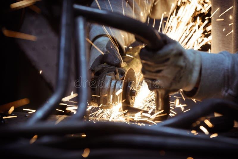 Metaal het malen op staalpijp met flits van vonken en de lijnen van metaal leiden dicht omhoog door buizen royalty-vrije stock afbeeldingen