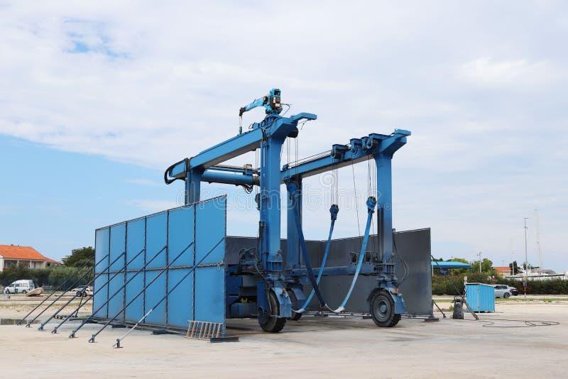 Metaal mobiele kraan voor de lancering van kleine schepen en jachten De ijzerstructuur is blauw Het uitrusten van een zeehaven en stock afbeelding