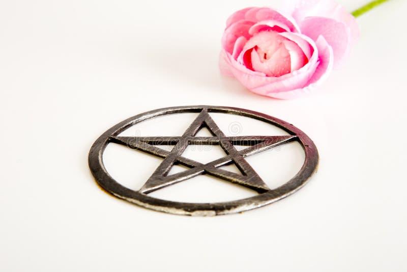Metaal pentagram met roze bloem op witte achtergrond royalty-vrije stock fotografie