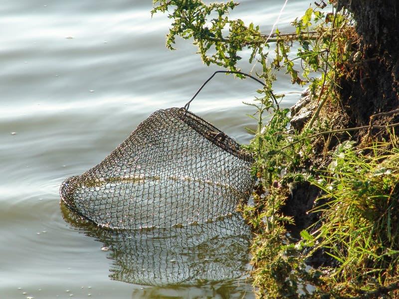 Metaal visserijtank in het water wordt verminderd dat stock foto's