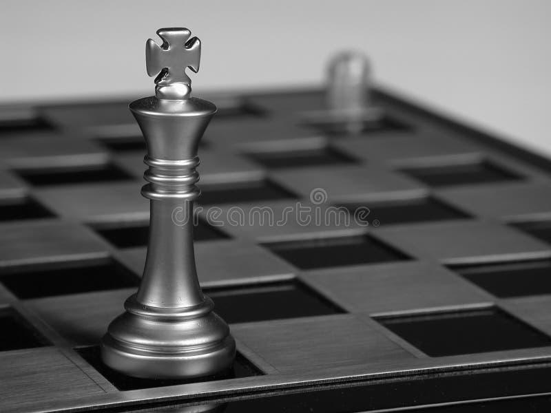 Metaal zwart-wit schaak op een schaakbord stock foto's