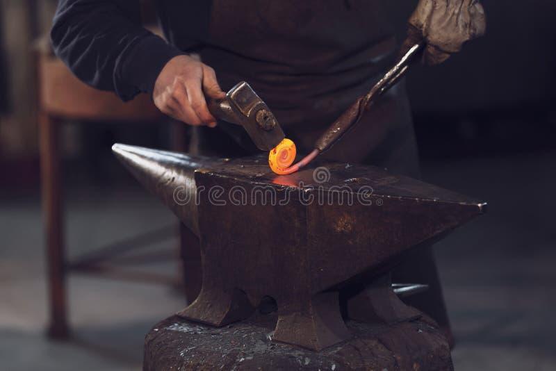 Metaalarbeider die een rol met heet metaal vormen royalty-vrije stock afbeelding