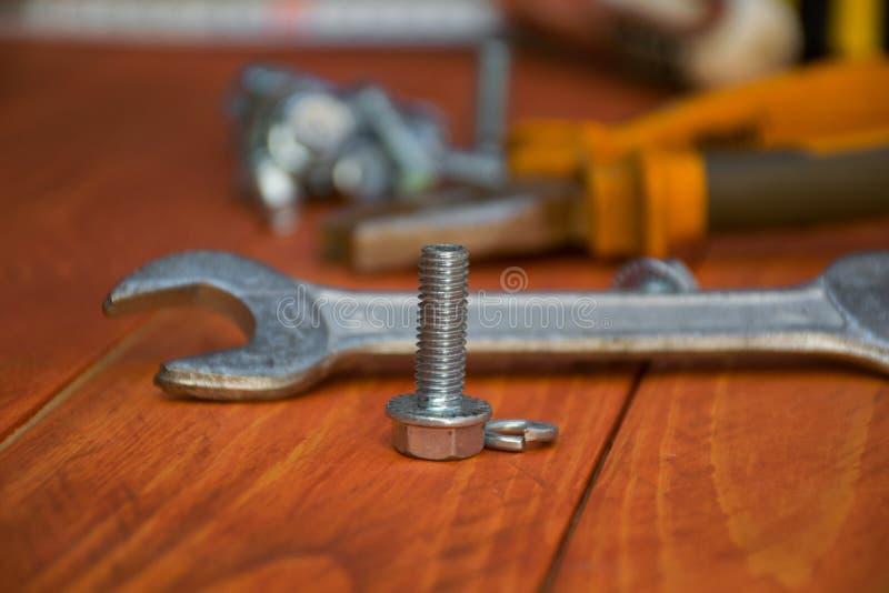 Metaalbout in de voorgrond met een moersleutel op de achtergrond stock afbeeldingen