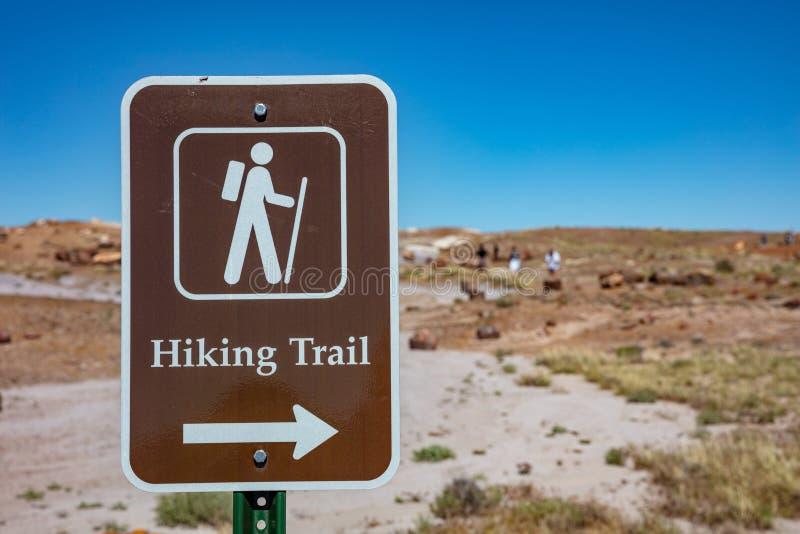 Metaalbruin bord met een witte kleurenkranker laat de bezoekers weten dat dit gebied een wandelend spoor heeft Petrified Forest,  stock foto