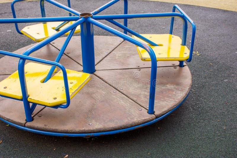Metaalcarrousel op de speelplaats met een rubberdeklaag stock afbeelding