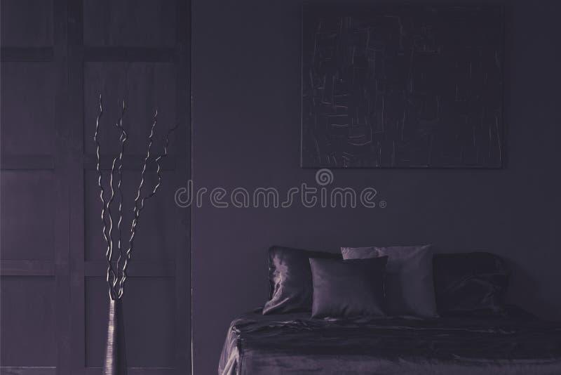 Metaaldecor naast bed in donker éénkleurig slaapkamerbinnenland met m stock afbeelding