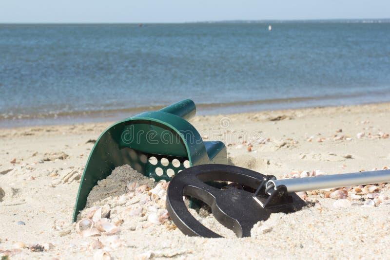 Metaaldetector en zandlepel op een zonnig strand stock afbeelding