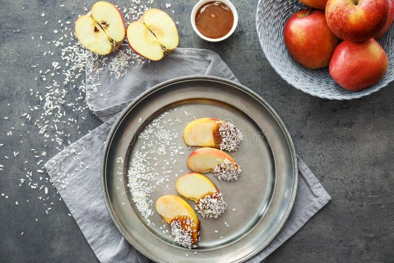 Metaaldienblad met de wiggen van de suikergoedappel en saus in kom op grijze lijst stock fotografie