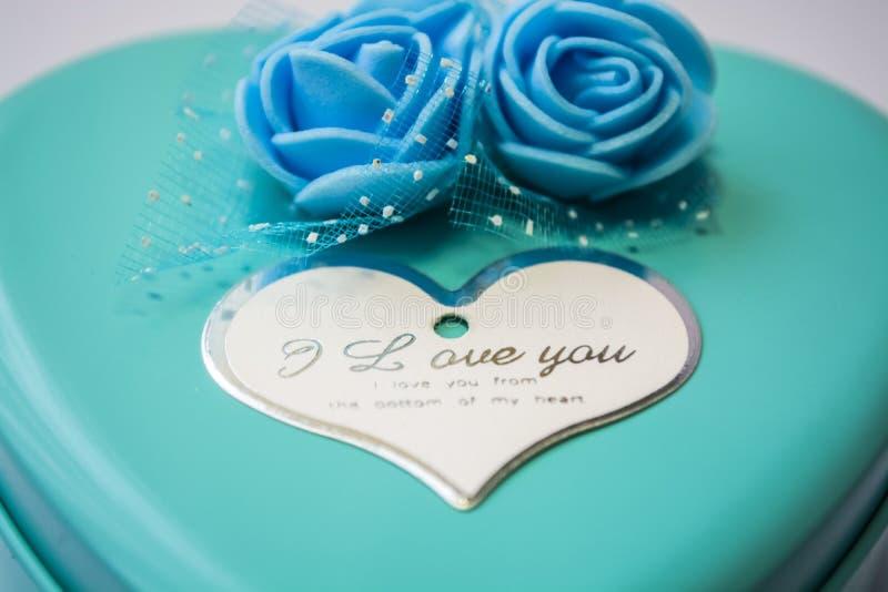 Metaaldoos in de vorm van hart met de inschrijvings 'I Liefde u 'en met rozen Blauwe kleur St de Dag van de valentijnskaart ` s royalty-vrije stock foto's
