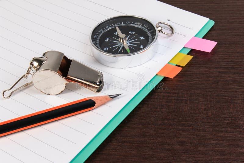 Metaalfluitje, potlood, kompas met notitieboekje op donkere houten rug stock foto