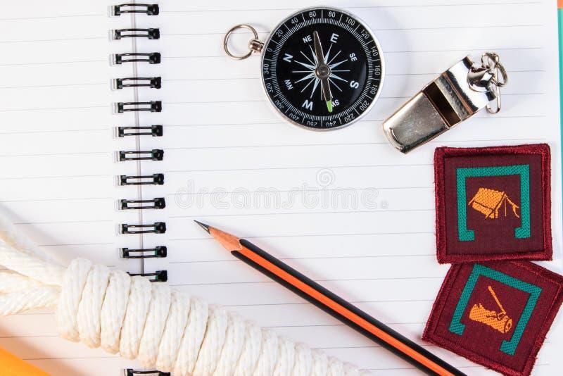 Metaalfluitje, verkennerskabel, notitieboekje, kompas, kenteken en potlood o stock fotografie