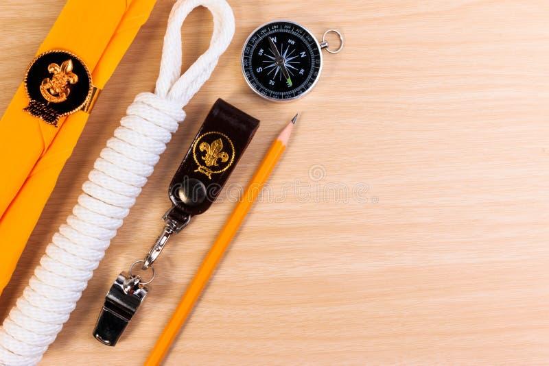 Metaalfluitje, verkennerssjaal, kabel, potlood en kompas op houten achtergrond royalty-vrije stock afbeelding