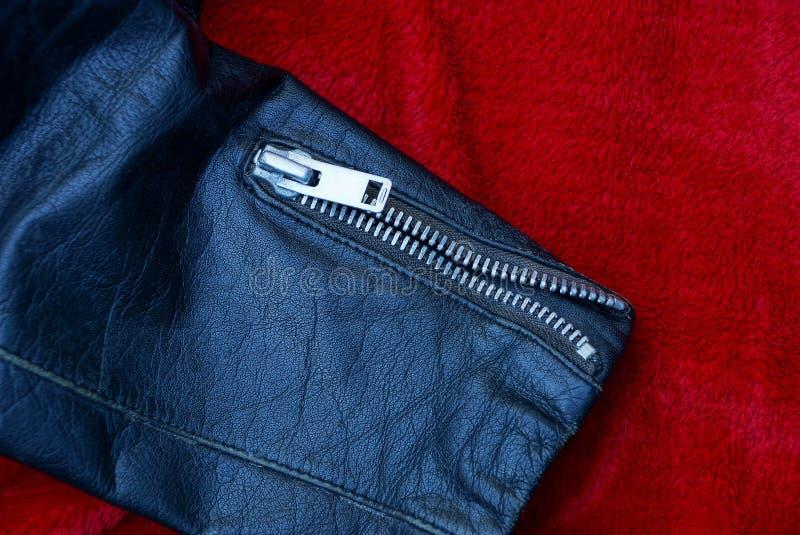 Metaalgesp op een zwart jasje van de leerkoker op rode doek stock foto's
