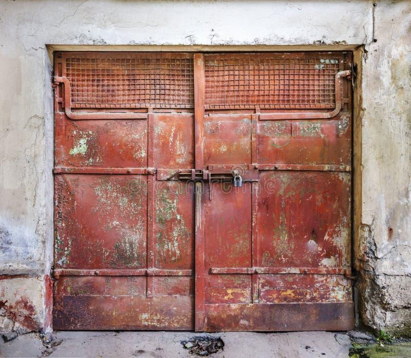Metaalhangslot op poorten van een de rode metaal oude garage stock afbeeldingen