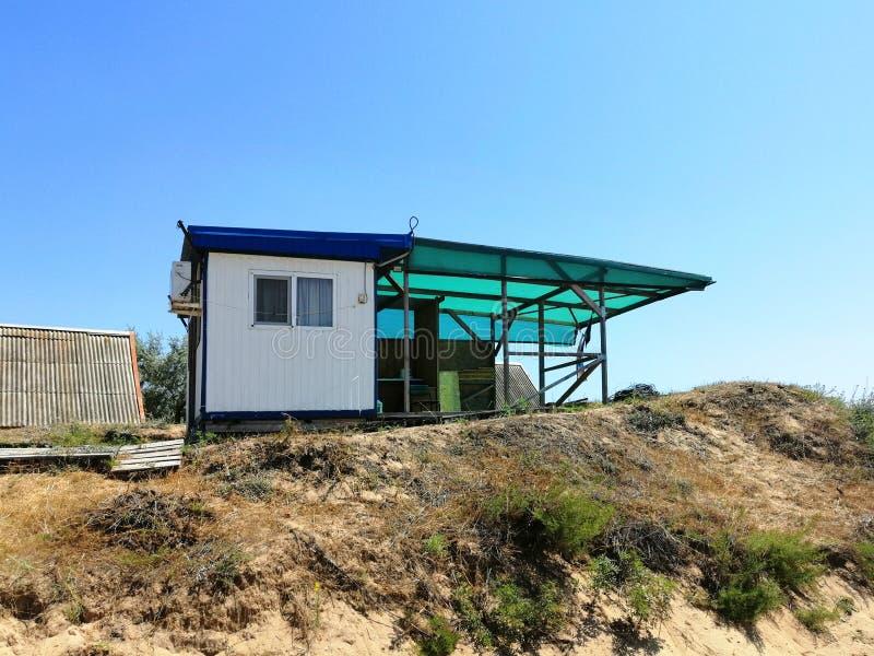 Metaalhuis met bijlage op de berg stock afbeelding