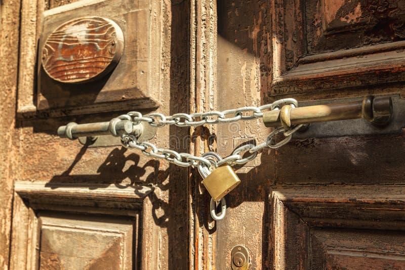 Metaalketting met een slot op een oude houten deur, close-up stock foto's