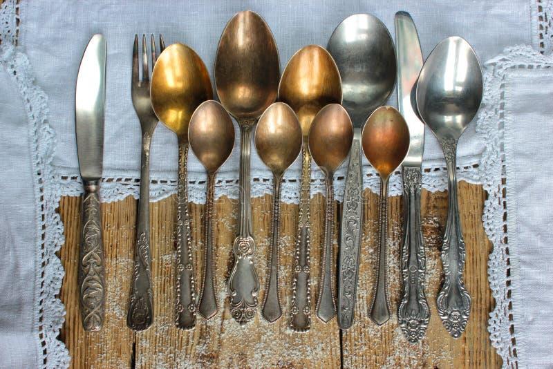 Metaallepels, vorken, messen, op een oude rustieke lijst stock foto's