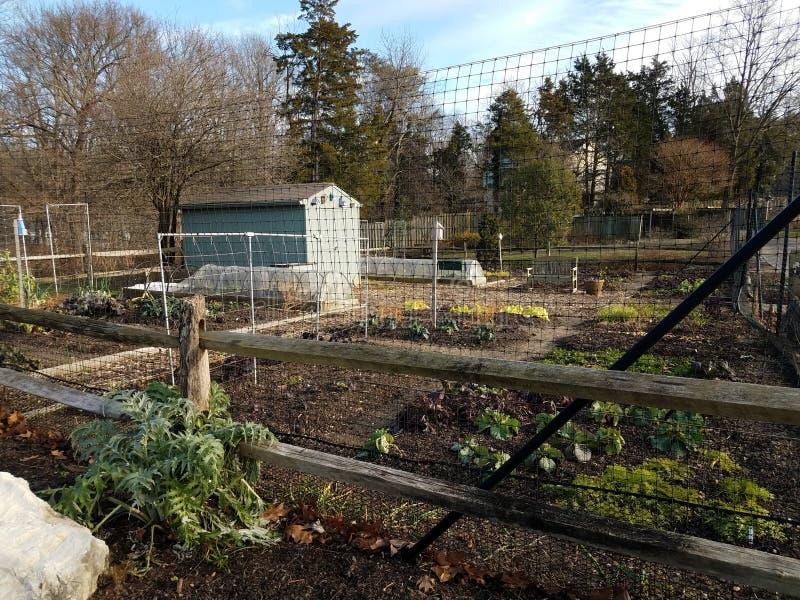 Metaalomheining met tuin en installaties en loods stock afbeelding