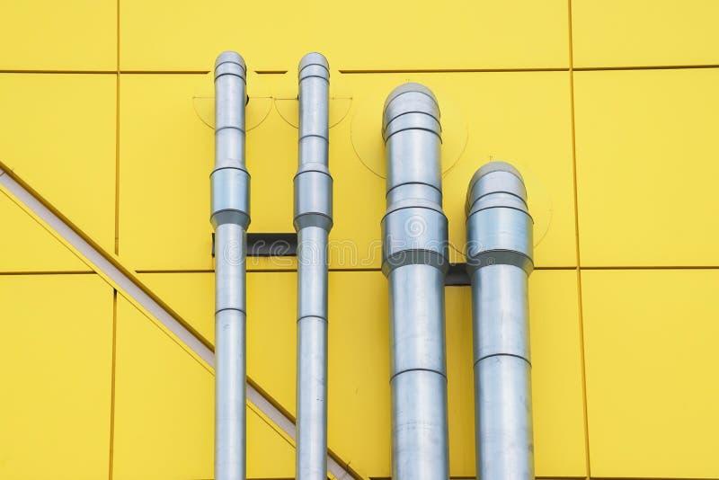 Metaalpijpen op de gele muur stock foto's