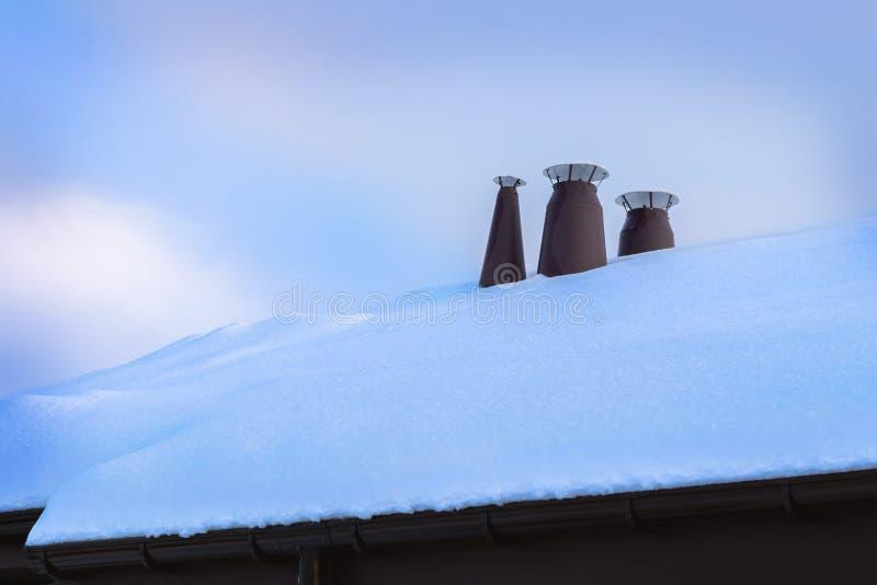 Metaalpijpen van het ventilatiesysteem op het dak van het gebouw met sneeuw wordt behandeld die stock foto