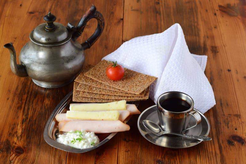 Metaalplaat met knäckebrood, kaas, kwark, ham, kersentomaat, kop van koffie, koffiepot op houten stock fotografie