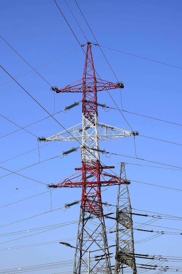 Metaalpylonen van machtslijnen met hoog voltage tegen een blauwe hemel stock afbeeldingen