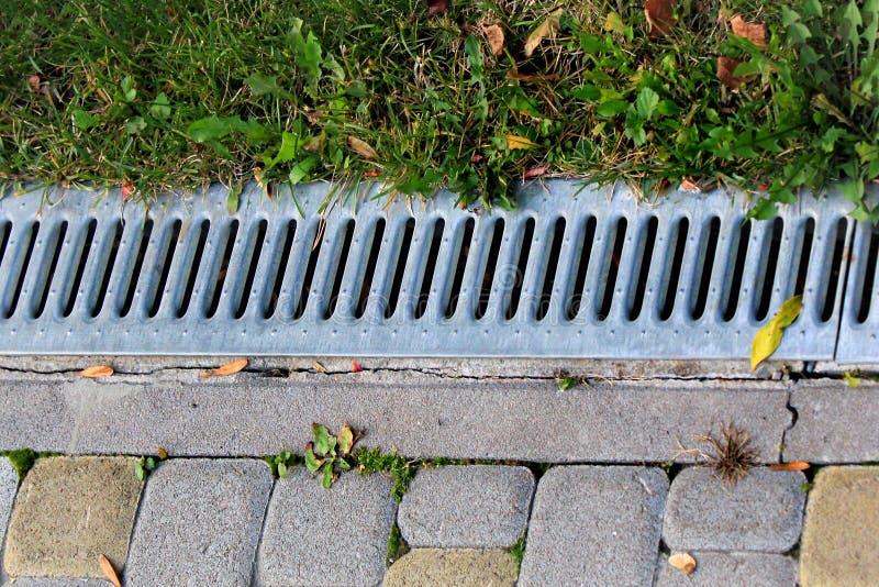 Metaalrooster van het systeem van de regenwaterdrainage in een park stock afbeeldingen