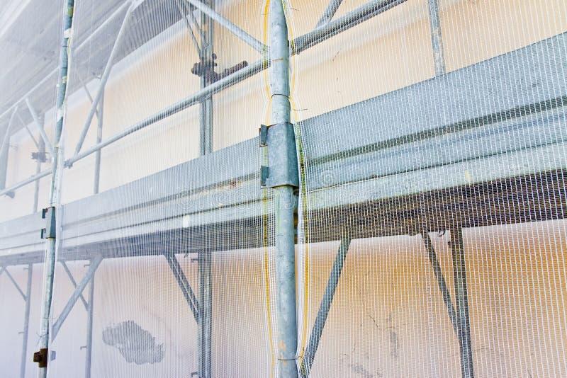 Metaalsteiger met plastic net voor de restauratie van een de bouwvoorgevel in een Italiaanse bouwwerf stock foto