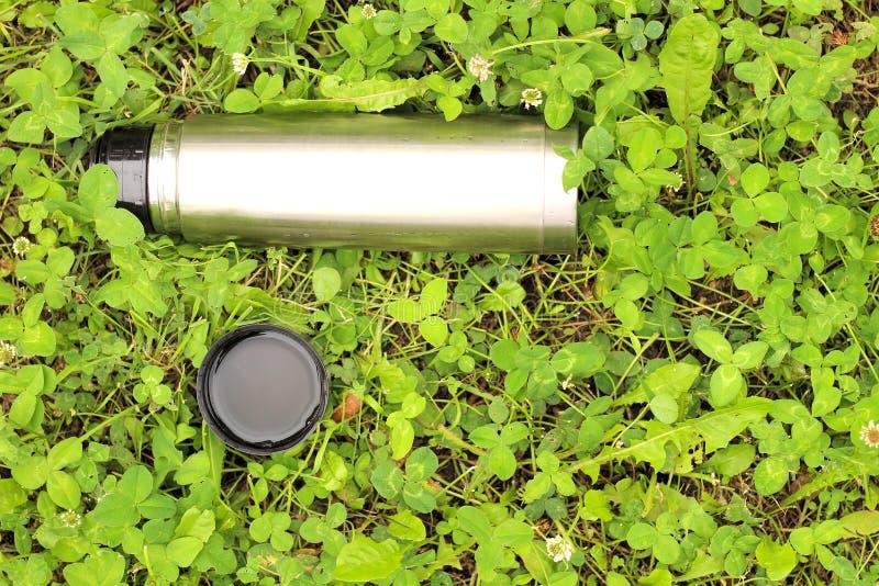 metaalthermosflessen met een deksel op het groene gras royalty-vrije stock afbeelding