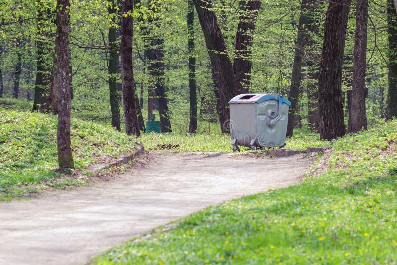 Metaalvuilnisbak in een openbaar park onder de bomen stock afbeelding