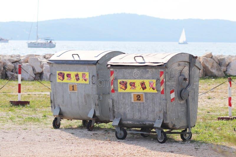 Metaalvuilnisbakken voor afval sorterende tribune op de pijler in de jachthaven tegen het overzees met varende jachten Daarna sch stock foto's