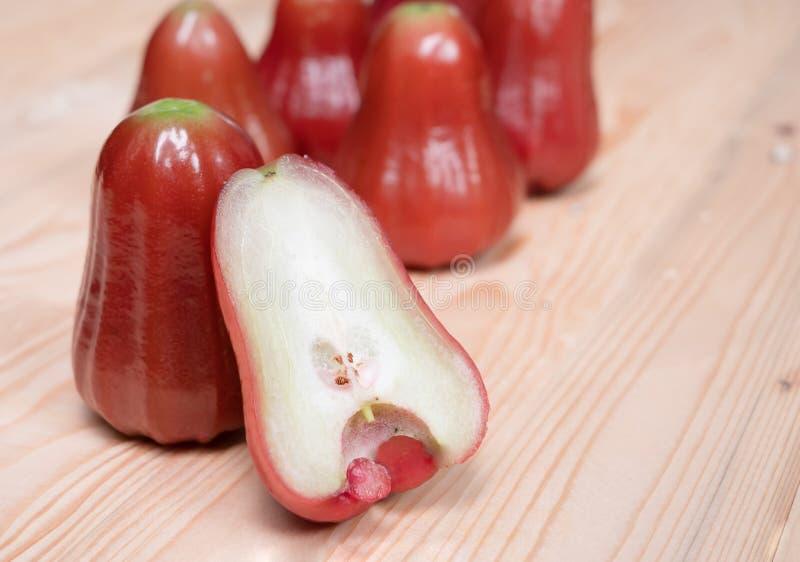 A metade ascendente próxima aumentou maçã na tabela de madeira foto de stock royalty free