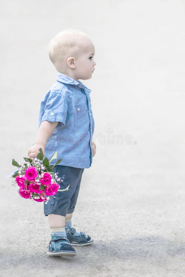 Metade-cara do retrato do bebê pequeno que está com o ramalhete cor-de-rosa das rosas exterior Cavalheiro pequeno com as flores q fotografia de stock royalty free