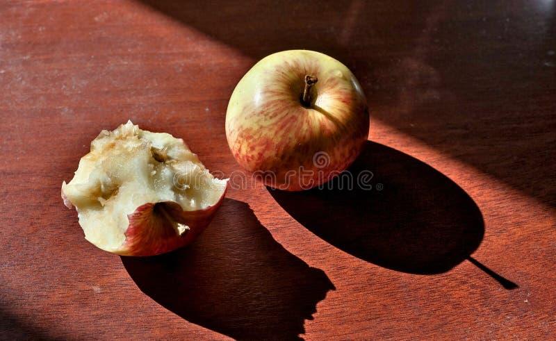 Metade comida e maçãs inteiras que encontram-se na tabela fotos de stock