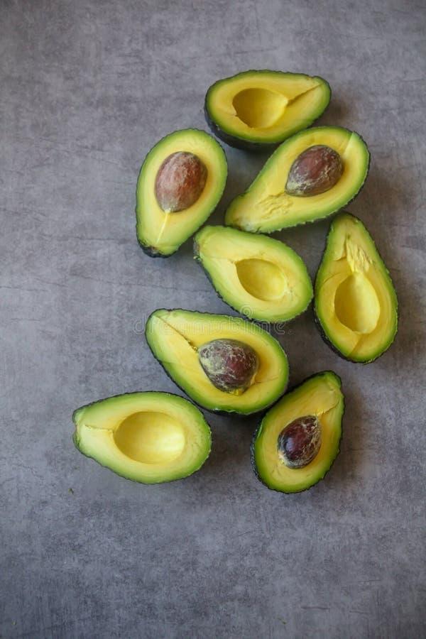 A metade cortou abacates maduros com a semente no fundo cinzento escuro, flt da vista superior coloca imagem de stock