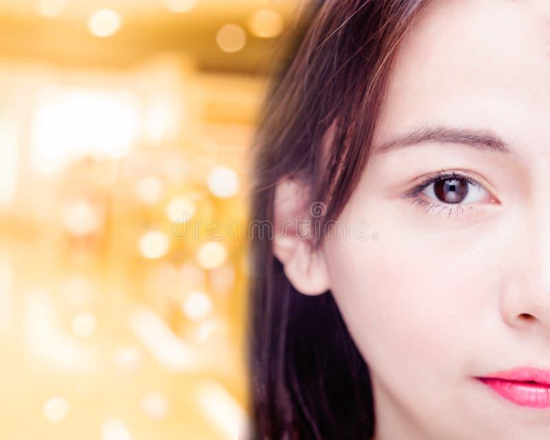Metade da cara asiática do ` s da mulher no fundo dourado imagens de stock