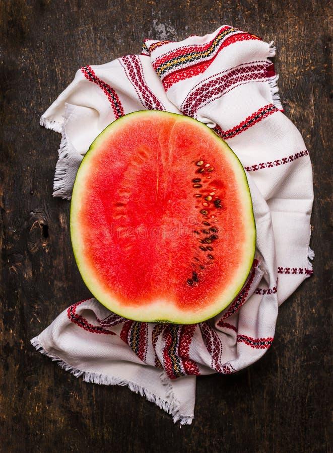 Metade da melancia vermelha madura com a toalha de cozinha no fundo de madeira rústico foto de stock royalty free