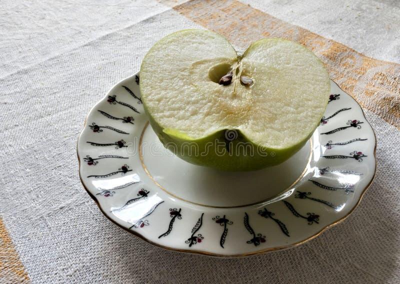 Metade de Apple verde nos pires fotografia de stock
