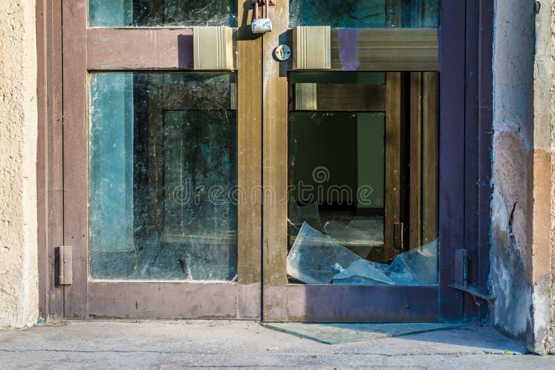 Metade de porta de vidro velha quebrada com fechamento de aço foto de stock
