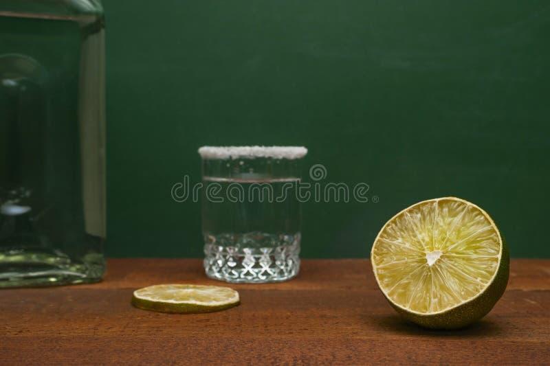 Metade de um cal com fatia borrada do cal, o tiro de prata do Tequila orlarado com sal e uma garrafa em uma tabela rústica de mad imagens de stock royalty free