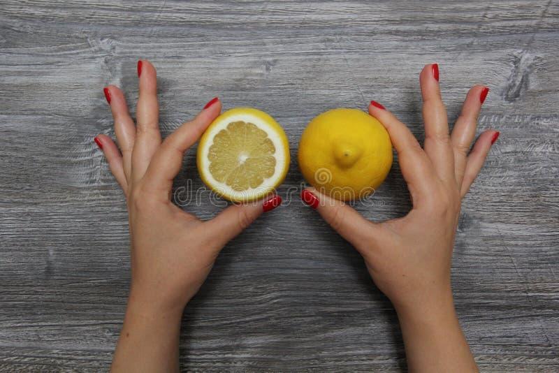 Metade de um limão na mão esquerda e limão inteiro no assistente fotos de stock