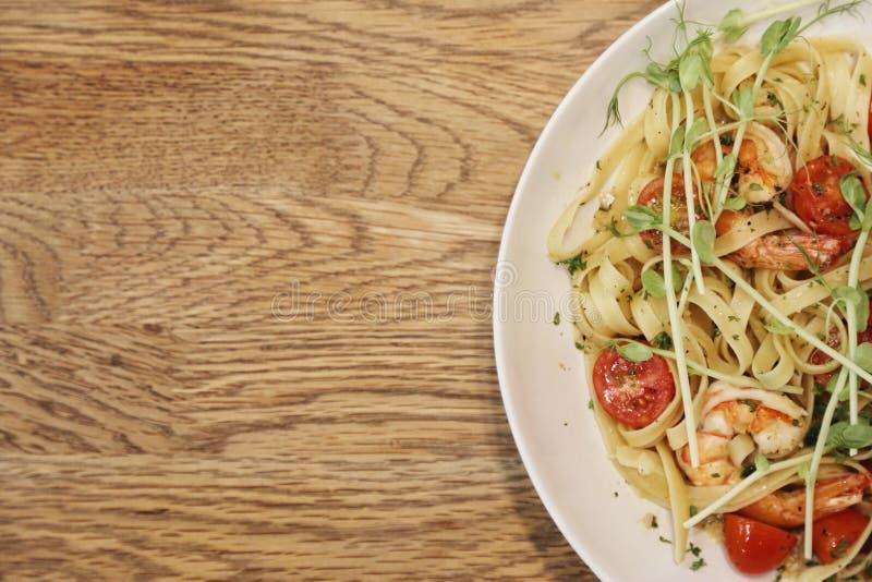 Metade de um prato branco com lagostim do camarão e do linguine dentro em uma tabela de madeira da vista superior imagem de stock