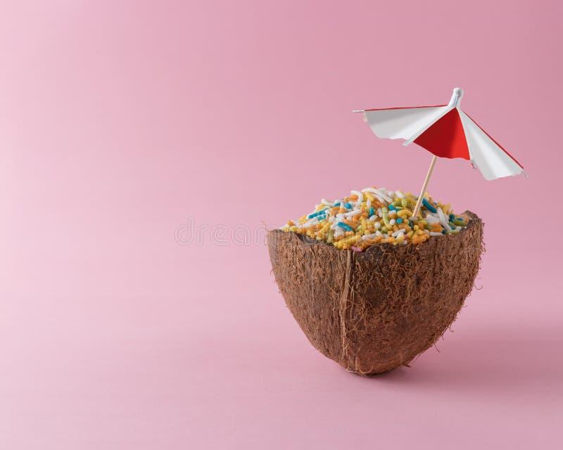 A metade do coco com colorido polvilha no fundo cor-de-rosa Conceito mínimo do alimento fotos de stock