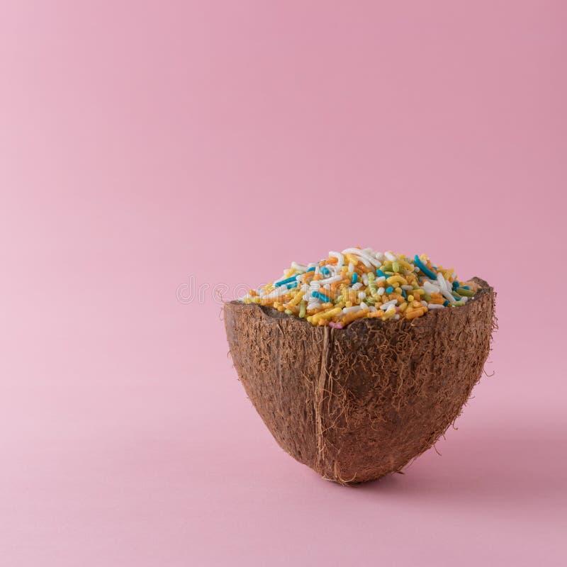 A metade do coco com colorido polvilha no fundo cor-de-rosa mínimo foto de stock royalty free