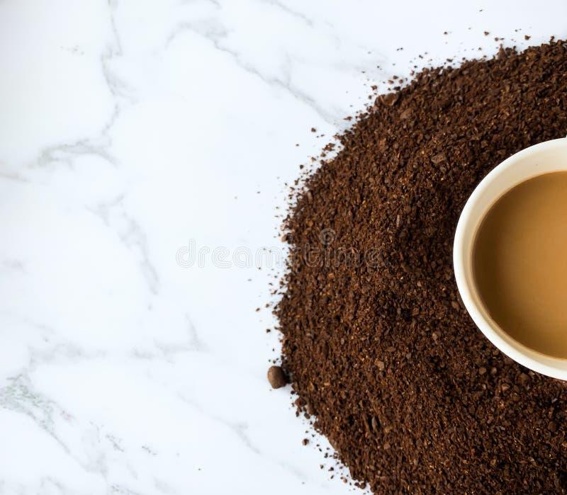 Metade do copo de café nos feijões de café roasted e à terra isolados no fundo de mármore branco imagem de stock